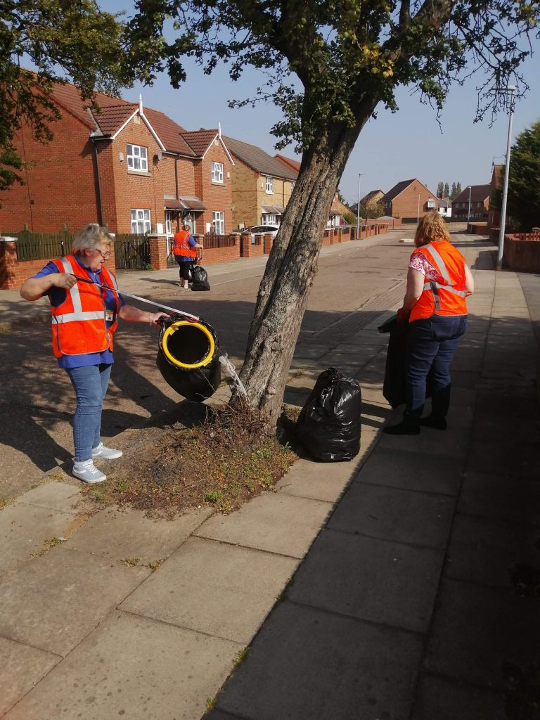 A photograph of some of the group members litter picking.