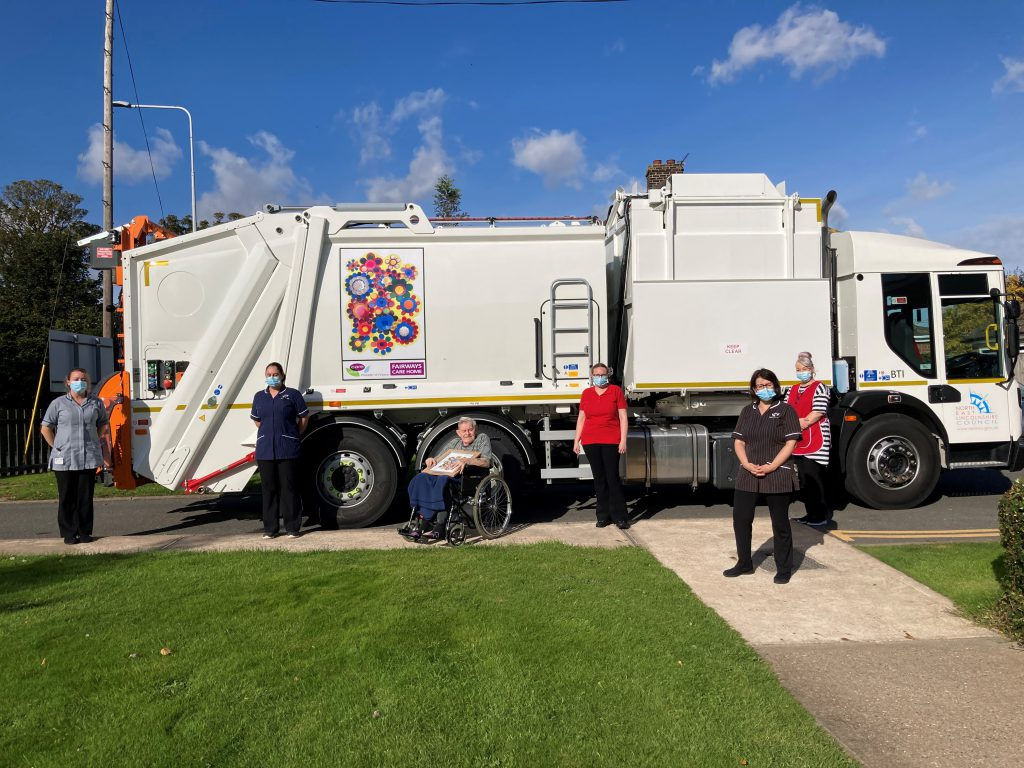 Staff and a resident from Fairways Care Home stand in front of the bin lorry with their artwork on.