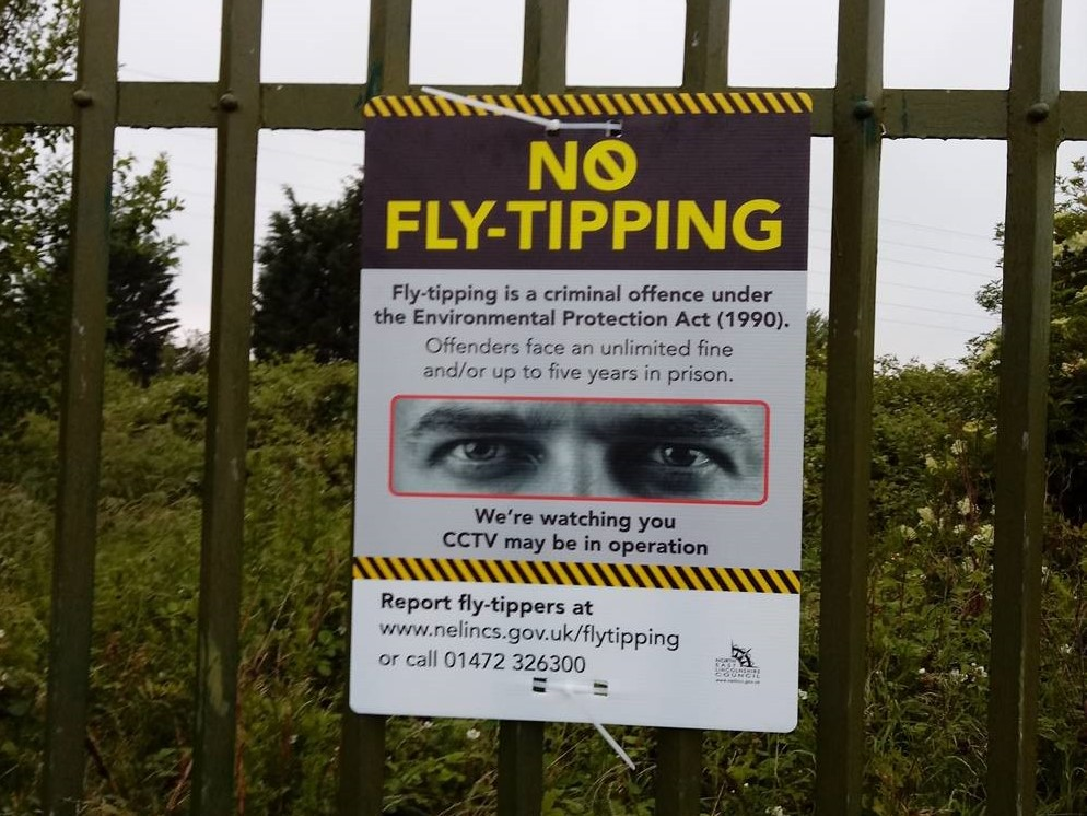 A 'no fly-tipping' warning sign attached to a metal fence.