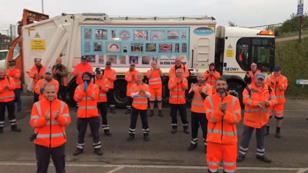 Refuse workers clapping in front of a wagon at Gilbey Road depot in Grimsby
