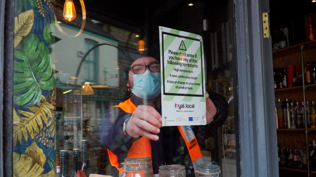 COVID Support Officer putting poster in shop window