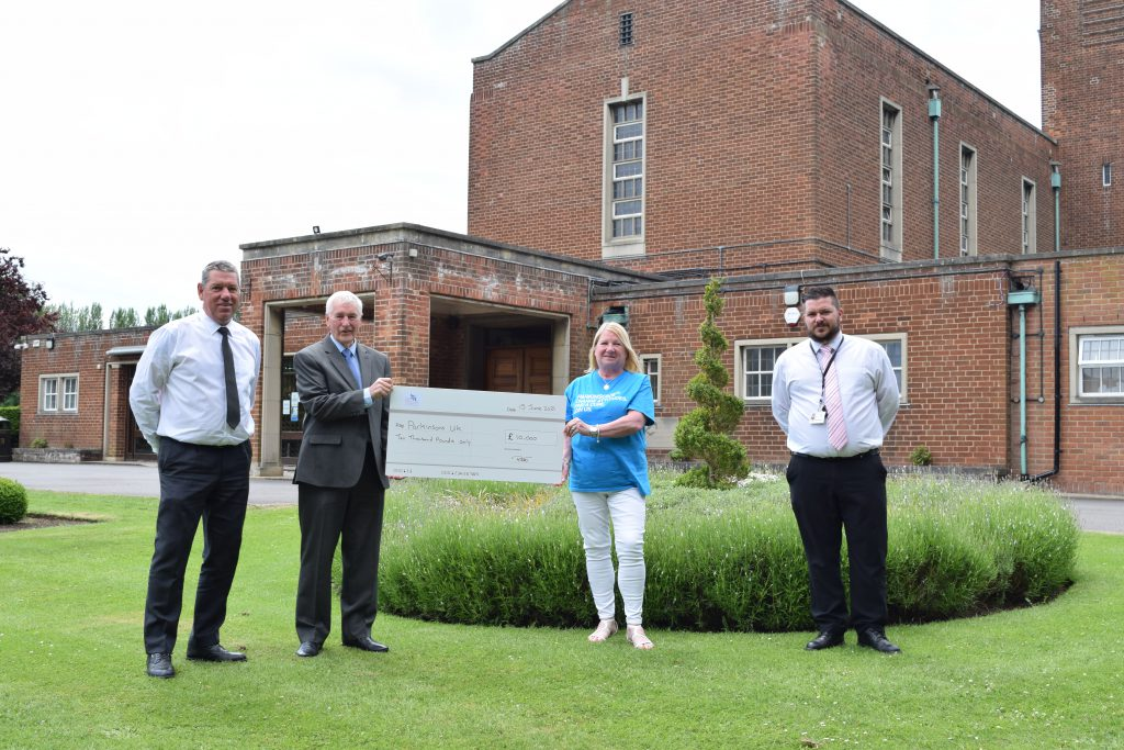A photo of representatives from Grimsby Crematorium presenting a cheque to Parkinsons UK.