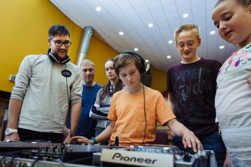 Young child at a mixing desk, surrounded by others