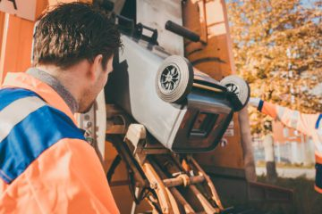 Worker emptying bin into waste vehicle
