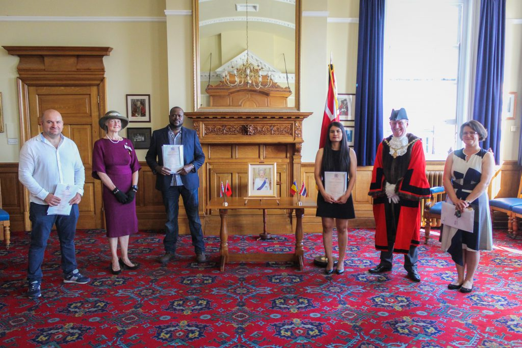 A photo of the Mayor and DLL presenting certificates in recognition of British Citizenship