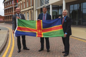 Leaders of Greater Lincolnshire, North Lincolnshire and North East Lincolnshire Councils holding a Lincolnshire flag